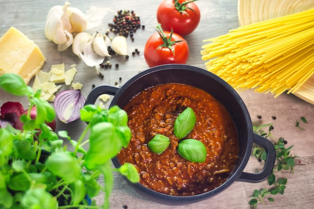 Black pot cooking sauce bolognese with ingredients on a wooden table