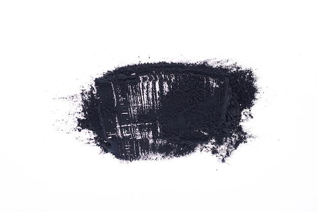 검은 가루 (숯 가루)가 흩어져 있습니다. 흰색 배경에 고립. 미세한 가루 숯의 느슨한 더미.