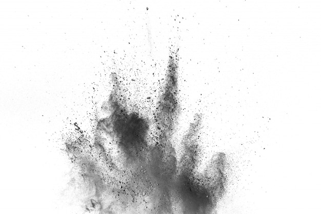 Black powder explosion against white background. charcoal dust particles exhale in the air.