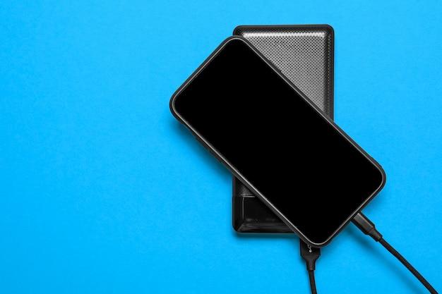 Black power bank заряжает смартфон, изолированный на синей поверхности