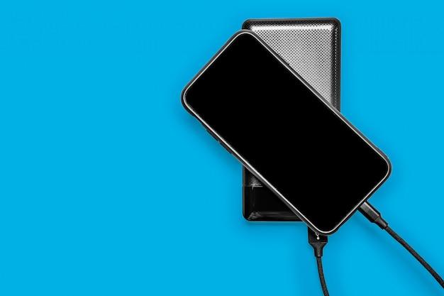 Банк black power заряжает смартфон, изолированный на classic blue pantone