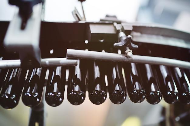 Черные преформы для выдувания пластиковых бутылок из пэт перемещаются по конвейерной ленте на фоне фабрики.