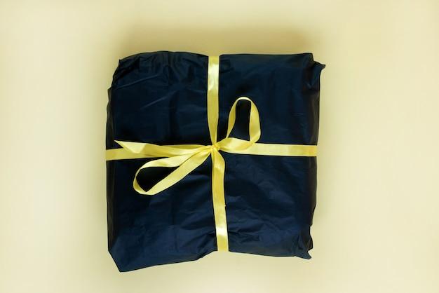 Черный настоящий ящик с золотой лентой. плоская планировка