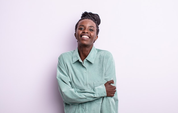 친절하고 긍정적이지만 불안한 태도로 수줍고 즐겁게 웃고 있는 흑인 예쁜 여성