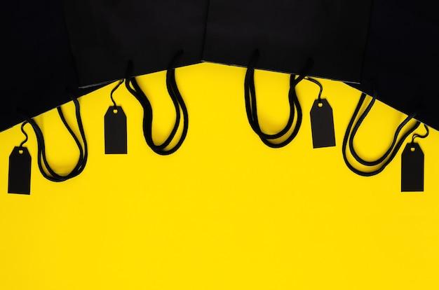 ブラックフライデーのショッピングセールのコンセプトのための黄色の背景にショッピング紙袋と黒の値札。
