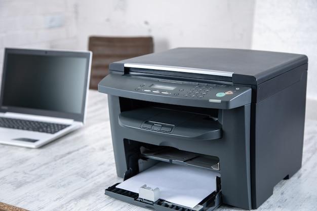 사무실 테이블에 검은 프린터와 컴퓨터