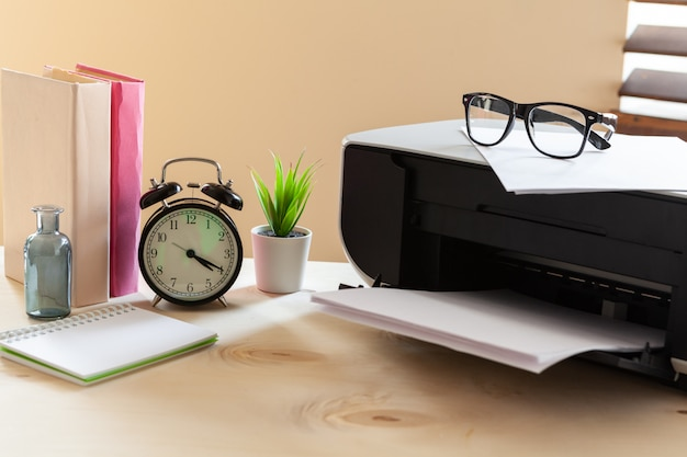 Black printer machine on a table with alarm clock and books