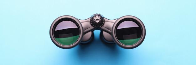 Black professional binoculars lying on blue background