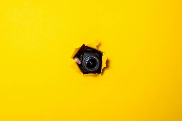 Black professional camera can be seen from a torn yellow cardboard