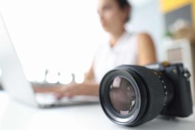 여성 노트북 근접 촬영 모바일 응용 프로그램의 배경에 누워 있는 검은색 전문 카메라
