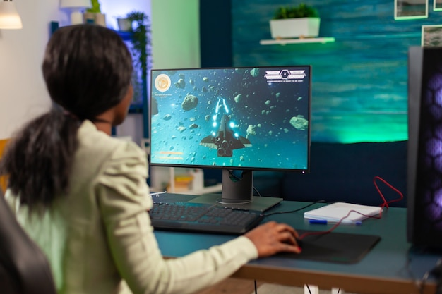흑인 전문 전자 스포츠 게이머가 의자에 앉아 경쟁에서 이기려고 합니다. 비디오 게임 토너먼트를 수행하는 경쟁적인 사이버 플레이어 여성은 전문 조이스틱을 사용합니다.