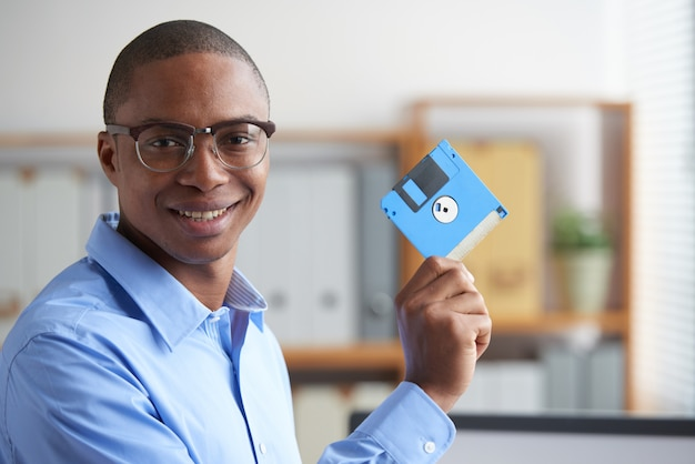 Black professional holding the floppy disk in the office