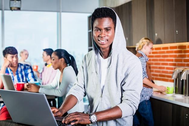 彼のラップトップ上のitスタートアップコーディングソフトウェアのラウンジにいる黒人プログラマー