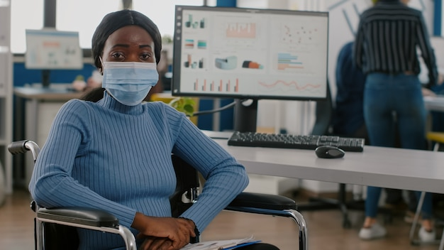 Black project manager with disabilities wearing face mask looking at camera