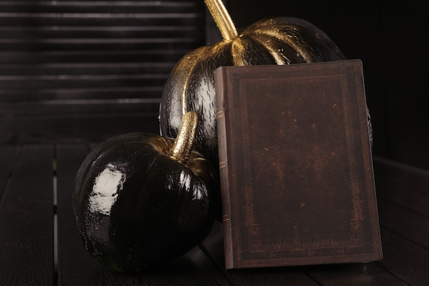 Черная тыква и книга. украшение дома на хэллоуин в современном стиле. по горизонтали.