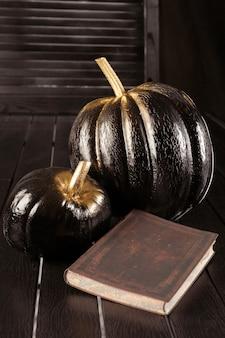 Черная тыква и книга. украшение дома на хэллоуин в современном стиле. вертикальный.