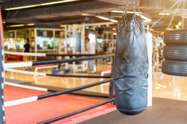 Black punching bag hanging in abstract blur of defocused boxing gym interior and fitness h