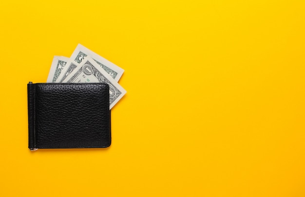 Black purse with dollar banknotes on yellow background. flat lay, top view, copy space.