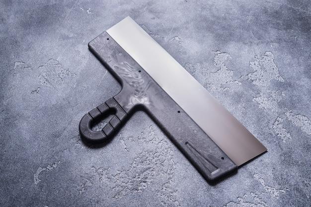 灰色の背景に黒のパテナイフ