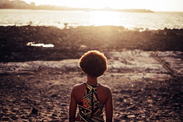 岩のビーチと海の夕日ライトゴールドの背景で後ろから見た素敵な髪の黒いレースモデル。旅行者と世界を愛する人々のための自由と放浪癖の概念