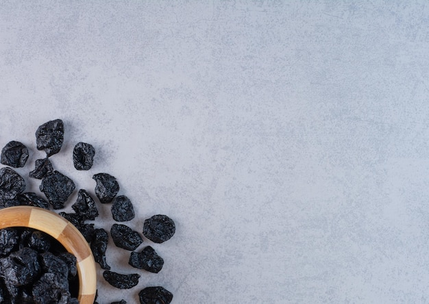 Черный изюм в деревянной чашке на бетонном фоне.