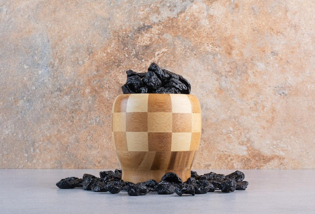 Uva passa nera in una tazza di legno su fondo di cemento.