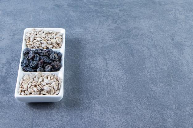 대리석 배경에 접시에 검은 건포도와 껍질을 벗긴 씨앗.