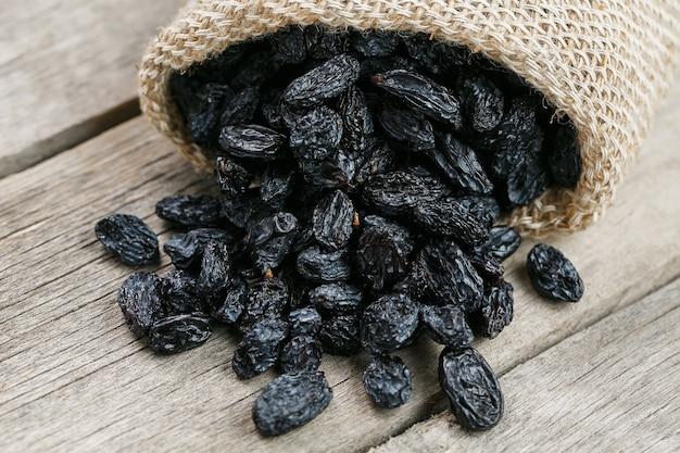 Black raisins in burlap bag over wooden gray table