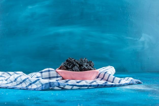 青いテーブルの上に、ティータオルのボウルに黒いレーズン。