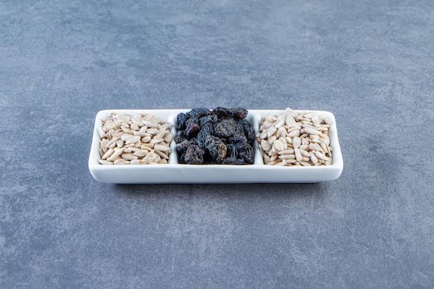 Uvetta nera e semi pelati in un piatto sulla superficie di marmo