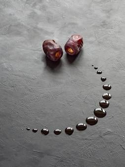 Черный рамадан фон с финиками даты и сироп вылил в форме полумесяца.