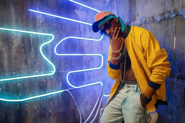 Black rapper in underpass neon light