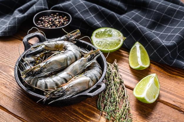 Черные сырые тигровые креветки, креветки на сковороде