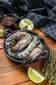 Черные сырые тигровые креветки, креветки на сковороде.