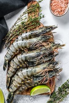 Черные сырые тигровые креветки, креветки на разделочной доске