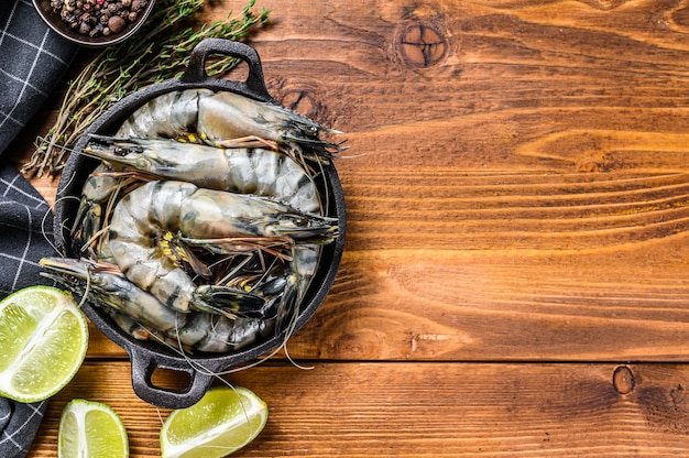 Black raw tiger prawns, shrimps in a pan. wooden background. top view. copy space.