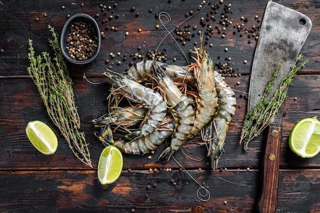 Черные сырые тигровые креветки, креветки с тимьяном и перцем.