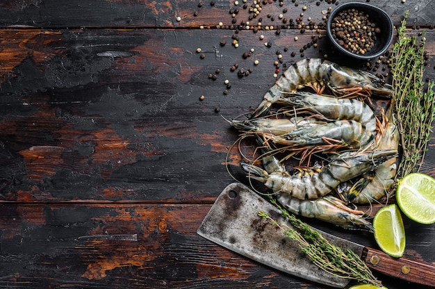 Black raw tiger prawns, shrimps with thyme and pepper. black wooden background. top view. copy space.