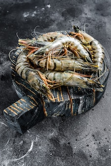 Black raw tiger shrimps. black background. top view.