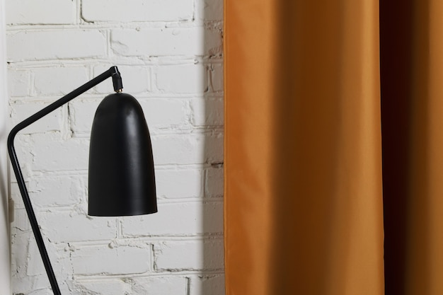 Black reading lamp on background of white brick wall and gold curtain