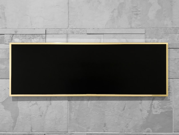 Black rectangle mock up with golden frame on gray marble brick wall background.