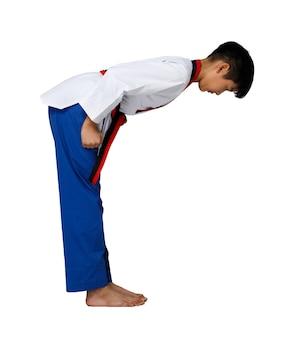 Черный красный пояс таэквондо каратэ малыш спортсмен-подросток показывает традиционный лук после боя в спортивной форме, мальчик 15 лет, студийное освещение на белом фоне, изолированный полный профиль