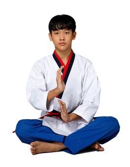 Черный красный пояс taekwondo karate kid спортсмен подросток шоу традиционной медитации сидит в спортивной форме платье, 15-летний мальчик, студийное освещение на белом фоне, изолированный полный профиль