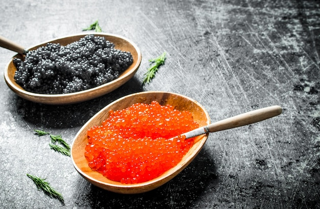 Black and red caviar in bowls with spoons. on black rustic surface