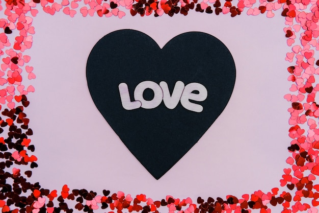 Black and red hearts with the words love on a pink background on valentine's day.