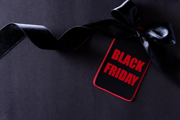 Black and red paper tag with ribbon on black, black friday.