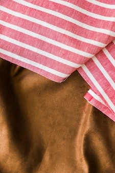 Black and red striped pattern fabric over the smooth brown textile