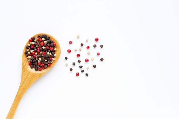Black, red and white peppercorns on white
