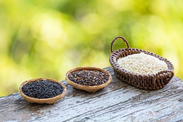 Black red and white sesame seeds on bokeh nature surface.