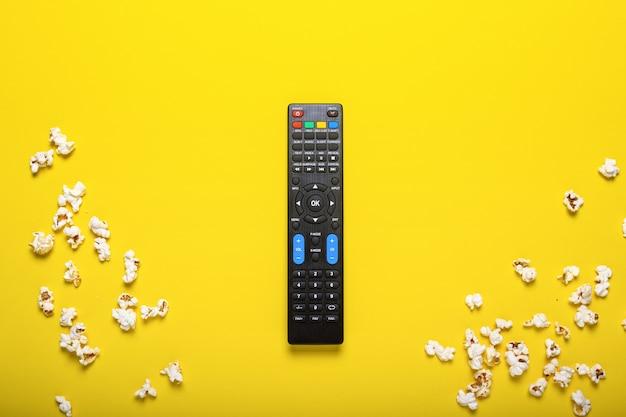 ポップコーン付きの黄色のテレビ、tvチューナーまたはオーディオシステムからの黒いリモコン